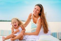 A fêmea e sua filha relaxam no backgraund do mar Fotografia de Stock