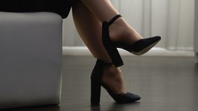 Fêmea elegante nos saltos altos que sentam-se com os pés cruzados, sapatas na moda, forma video estoque