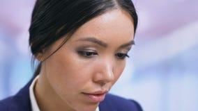 Fêmea em documentos da leitura do businesswear, trabalhador de escritório no local de trabalho, close up filme
