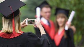 Fêmea em melhores amigos acadêmicos do película do vestido e do chapéu no telefone, dia de graduação vídeos de arquivo