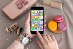 A fêmea entrega a joia que guarda o telefone com apps dos ícones da tela home Imagens de Stock Royalty Free