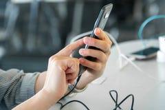 A fêmea entrega o holdingsmartphone ao carregá-lo em um pla do público Imagem de Stock Royalty Free
