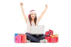 Fêmea entusiasmado com o chapéu de Santa que trabalha no portátil e nos presentes ao redor Fotografia de Stock Royalty Free