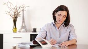 A fêmea escreve uma letra na sala de jantar com método clássico do pena-papel:) vídeos de arquivo
