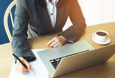 A fêmea está trabalhando na tabela de madeira Foto de Stock Royalty Free