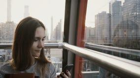 fêmea europeia do turista 4K na cabine do bonde do ar Mulher de negócios bonita com o smartphone no teleférico da ilha de New Yor video estoque