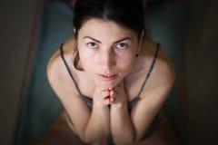 Fêmea europeia nova lindo no fundo escuro, guardando as mãos no namaste ou na oração, mantendo os olhos abertos, ao praticar  imagens de stock