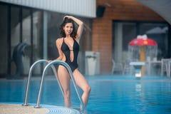 A fêmea feliz atrativa está levantando na piscina em um roupa de banho preto no recurso fotografia de stock royalty free