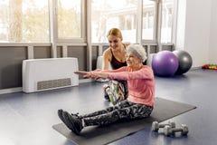 Fêmea feliz que ajuda irradiando o aposentado que faz o exercício imagens de stock