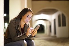 Fêmea feliz que usa um telefone esperto na noite na rua imagem de stock