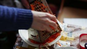 A fêmea fricciona cenouras em um ralador em uma placa de desbastamento vídeos de arquivo