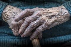 A fêmea idosa entrega o tratamento de mãos e o bastão Imagens de Stock Royalty Free