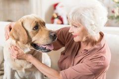 A fêmea idosa positiva está sentando-se com animal de estimação imagem de stock royalty free