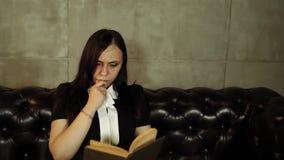Fêmea lendo um livro no sofá Mulher 20s do retrato usando o livro de leitura ao descansar e ao sentar-se no sofá em brilhante filme