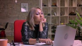 A fêmea loura cacasian furada está olhando sua tela e para aterrar para baixo em seu desktop, refrigerando no escritório do tijol video estoque