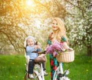 Fêmea loura com a bicicleta da cidade com o bebê na cadeira da bicicleta fotografia de stock