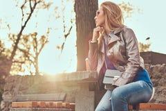 A fêmea loura elegante relaxa exterior, sentando-se no banco no parque da cidade contra uma luz solar brilhante imagens de stock royalty free