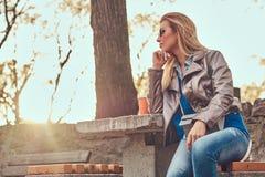 A fêmea loura elegante relaxa exterior, sentando-se no banco no parque da cidade contra uma luz solar brilhante foto de stock royalty free