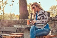 A fêmea loura na moda do blogger relaxa exterior, sentando-se no banco no parque da cidade contra uma luz solar brilhante foto de stock royalty free