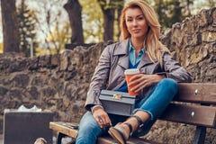 A fêmea loura na moda relaxa o café afastado exterior, bebendo ao sentar-se no banco no parque da cidade fotos de stock