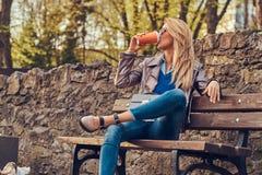 A fêmea loura na moda relaxa o café afastado exterior, bebendo ao sentar-se no banco no parque da cidade imagem de stock