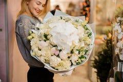 A fêmea loura sorri e guarda um ramalhete com orquídeas brancas, eustoma, kraspediya, rosas brancas Fotografia de Stock Royalty Free