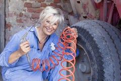 A fêmea madura mecânica infla o pneu foto de stock royalty free