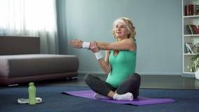A fêmea madura saudável que faz a aptidão exercita na esteira da ioga, treinando em casa fotos de stock royalty free