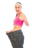 Fêmea magro que puxa calças de brim desproporcionados Imagem de Stock Royalty Free
