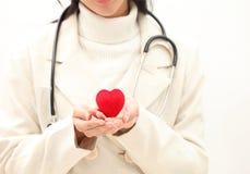 A fêmea medica as mãos do ` s que guardam e que cobrem o coração vermelho do brinquedo Docto fotos de stock royalty free