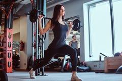 A fêmea moreno bonita em fazer do sportswear investe contra com barbell em um clube ou em um gym de aptidão imagem de stock
