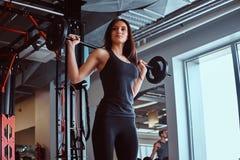 A fêmea moreno bonita no sportswear guarda um barbell ao treinar em um clube ou em um gym de aptidão imagem de stock