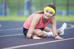 Fêmea moreno caucasiano em Sportgear atlético que tem os pés que esticam Excercises fora foto de stock