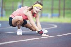 Fêmea moreno caucasiano nova em Sportgear atlético que tem o pé fotos de stock