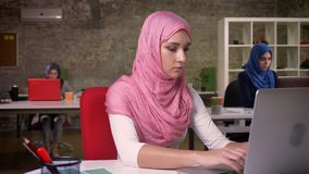 A fêmea muçulmana bonita no hijab agradável cor-de-rosa está datilografando no computador concentrado, sentando-se no desktop, tr filme