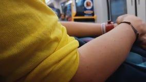 Fêmea na blusa amarela que senta-se no trem da cidade, indo em casa, estilo de vida urbano filme