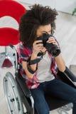 Fêmea na cadeira de rodas usando a câmera fotos de stock royalty free
