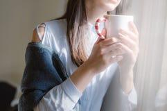 Fêmea na camisa azul pela janela com copo do coffe imagem de stock royalty free