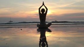 Fêmea na pose da meditação da ioga em por do sol surpreendente no mar
