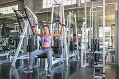 Fêmea no gym esporte, aptidão, halterofilismo, mulher que exercita e que dobra os músculos na máquina no gym Menina asiática Meni imagens de stock