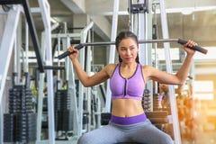 Fêmea no gym esporte, aptidão, halterofilismo, mulher que exercita e que dobra os músculos na máquina no gym Menina asiática Meni fotografia de stock royalty free