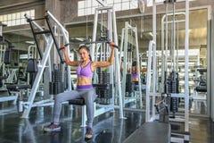 Fêmea no gym esporte, aptidão, halterofilismo, mulher que exercita e que dobra os músculos na máquina no gym Menina asiática Meni imagens de stock royalty free