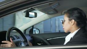 Fêmea no terno de negócio que senta-se no carro que é no dever, segurança nacional, agente filme