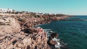 Fêmea no vestido vermelho em penhascos rochosos com mãos aos lados no ar Ondas fortes brancas do mar que batem o litoral que cria filme