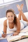 Fêmea nova atrativa que estuda em casa no assoalho fotos de stock