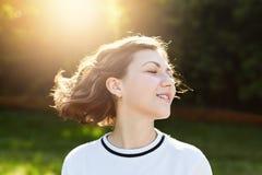 Fêmea nova atrativa repousante que fecha seus olhos com o prazer que admira o por do sol e o ar fresco exteriores Mulher bonita c imagens de stock royalty free