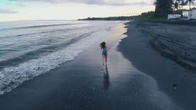 A fêmea nova bonita corre ao longo da praia do oceano com areia preta e acena no por do sol em Bali, vídeo 4K dos aviões video estoque