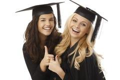Graduados bonitos da fêmea que mostram o sinal aprovado Fotos de Stock Royalty Free