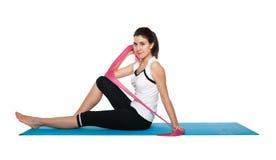 Fêmea nova bonita que exercita em um azul matt Foto de Stock