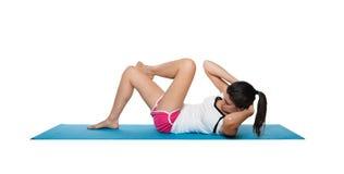 Fêmea nova bonita que exercita em um azul matt Fotografia de Stock Royalty Free
